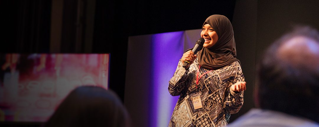 muslim woman talking on stage into a microphone looking happy