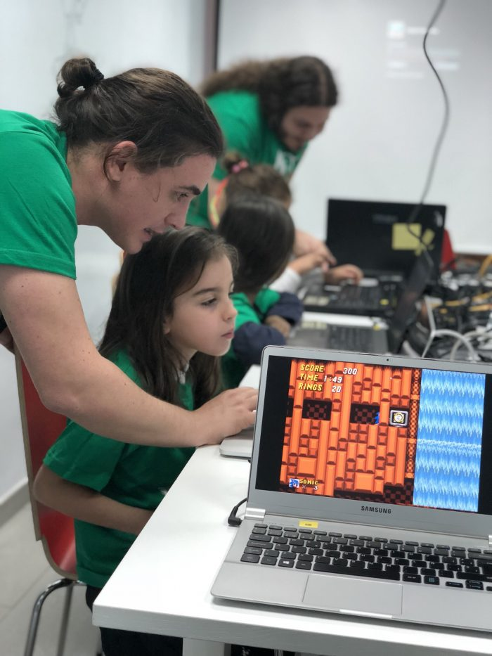 A Man helps a child to code a video game teaching them about it