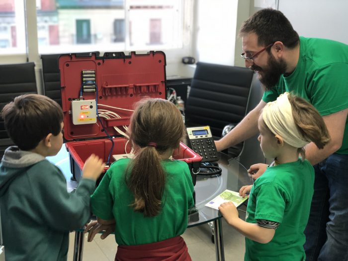 a man helps three children use a technical kit teaching them about it on our 5th annual Kidzday