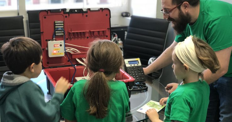a man helps three children use a technical kit teaching them about it