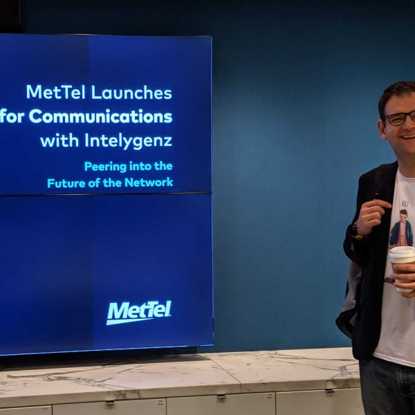 Intelygenz co-founder pepe in front of a Met Tel and Intelygenz sign